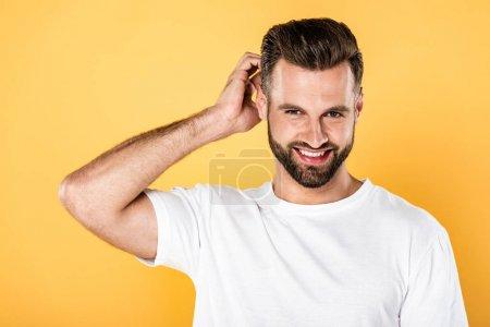 Photo pour Heureux bel homme en t-shirt blanc tête à gratter isolé sur jaune - image libre de droit