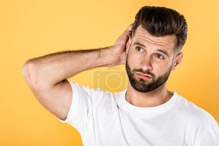 thoughtful man in white t-shirt scratching head isolated on yellow