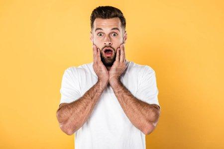 Photo pour Homme beau effrayé en t-shirt blanc isolé sur jaune - image libre de droit