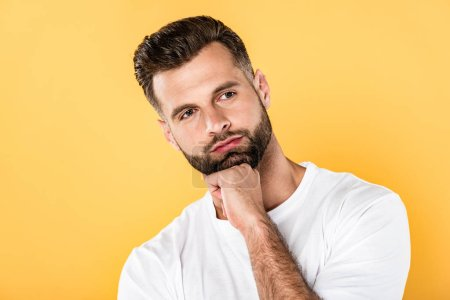 Photo for Pensive handsome man in white t-shirt looking away isolated on yellow - Royalty Free Image
