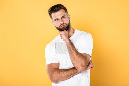 Photo for Pensive man in white t-shirt looking away isolated on yellow - Royalty Free Image