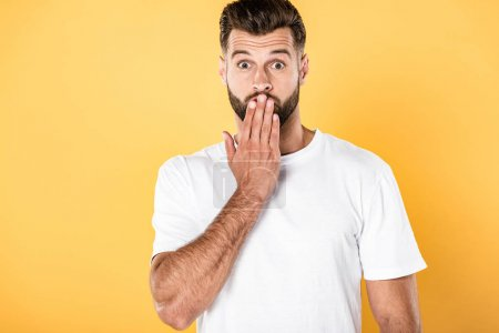 Photo for Shocked handsome man in white t-shirt with hand on mouth isolated on yellow - Royalty Free Image