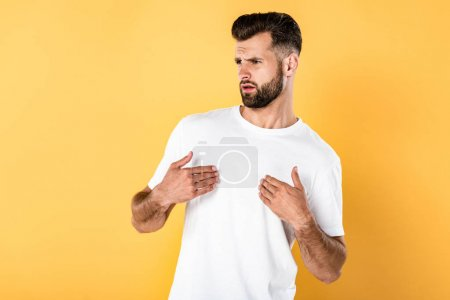 Photo for Indignant handsome man in white t-shirt isolated on yellow - Royalty Free Image
