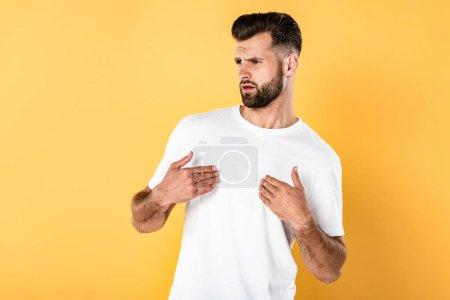 Photo pour Beau homme indigné dans le t-shirt blanc d'isolement sur le jaune - image libre de droit