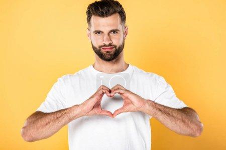 Photo pour Bel homme dans le t-shirt blanc affichant le signe de coeur avec des mains d'isolement sur le jaune - image libre de droit