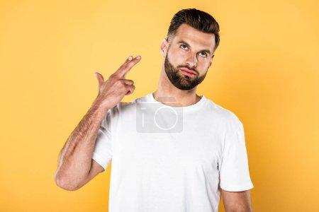 Photo pour Bel homme dans le t-shirt blanc affichant le pistolet de doigt d'isolement sur le jaune - image libre de droit