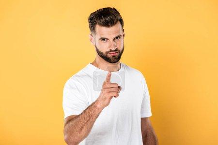 Photo pour Sérieux bel homme en t-shirt blanc pointant du doigt la caméra isolée sur jaune - image libre de droit