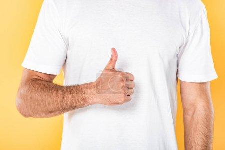 Photo pour Vue raccourcie de l'homme dans le t-shirt blanc affichant le pouce vers le haut d'isolement sur le jaune - image libre de droit