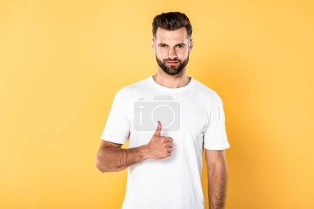 Foto de Hombre guapo en camiseta blanca mostrando pulgar hacia arriba aislado en amarillo - Imagen libre de derechos