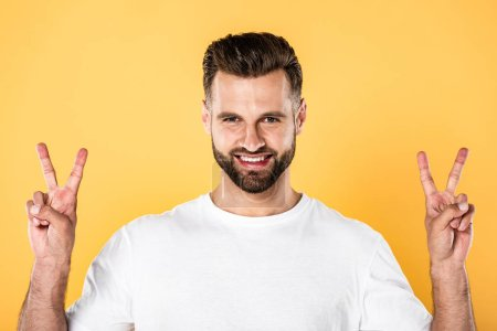 Photo for Smiling handsome man in white t-shirt looking at camera and showing peace signs isolated on yellow - Royalty Free Image