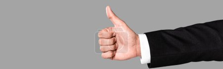 Photo for Partial view of businessman in black suit showing thumb up isolated on grey, panoramic shot - Royalty Free Image