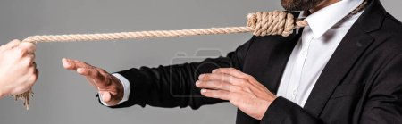 Photo for Cropped view of businessman in black suit with noose on neck showing stop gesture to murderer with rope isolated on grey, panoramic shot - Royalty Free Image