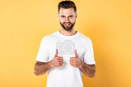 Foto de Sonriendo hombre guapo en camiseta blanca mirando a la cámara y mostrando los pulgares hacia arriba aislados en amarillo - Imagen libre de derechos