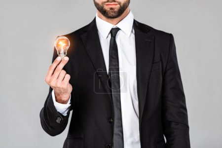 Photo for Cropped view of businessman in black suit holding glowing light bulb isolated on grey - Royalty Free Image