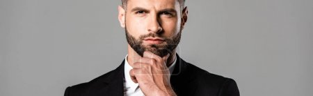 plano panorámico de empresario guapo pensativo en traje negro aislado en gris