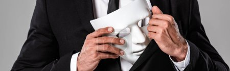 cropped view of businessman in black suit holding white mask isolated on grey, panoramic shot
