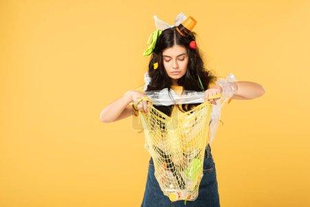 Photo pour Fille émotive avec la poubelle dans le sac de fixation de cheveux avec des ordures d'isolement sur le jaune - image libre de droit