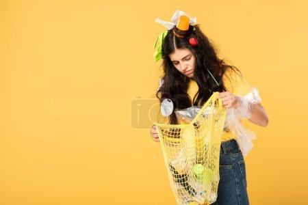 Photo pour Frustré fille avec poubelle dans les cheveux tenant sac avec des ordures isolées sur jaune - image libre de droit