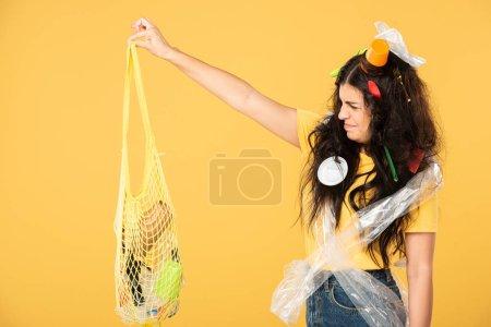 Photo pour Femme frustréavec des ordures dans le sac de fixation de cheveux avec la poubelle d'isolement sur le jaune - image libre de droit