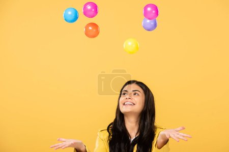 excited girl with colorful balls, isolated on yellow