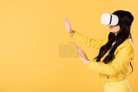 Photo for Emotional girl using Virtual reality headset, Isolated On yellow - Royalty Free Image