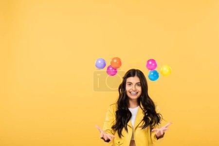 Foto de Atractiva chica sonriente con bolas de colores, aislada en amarillo - Imagen libre de derechos
