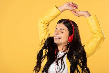 Photo pour Belle femme gaie dansant et écoutant la musique avec des écouteurs, d'isolement sur le jaune - image libre de droit