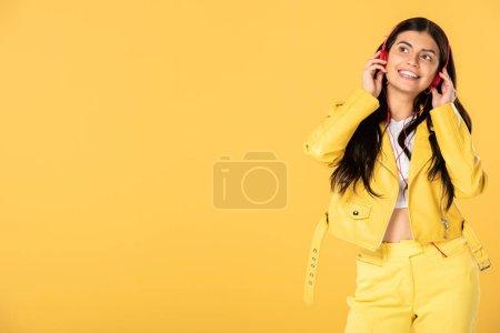 Photo pour Jolie jeune femme écoutant la musique avec le casque, dissié sur le jaune - image libre de droit