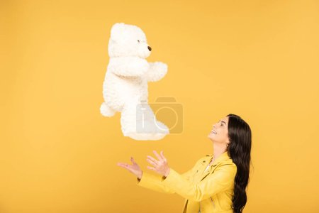 attractive girl throwing up teddy bear, Isolated On yellow