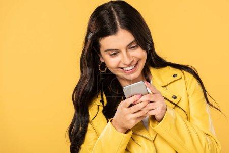 Photo pour Attrayant brunette fille en utilisant smartphone, isolé sur jaune - image libre de droit