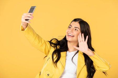 Photo pour Fille brune agitant et ayant le chat vidéo sur le smartphone, d'isolement sur le jaune - image libre de droit