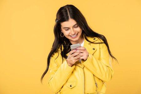 Photo pour Gai brunette fille en utilisant smartphone, isolé sur jaune - image libre de droit