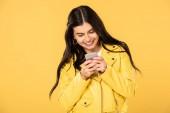 """Постер, картина, фотообои """"веселая брюнетка девушка с помощью смартфона, изолированные на желтый"""""""