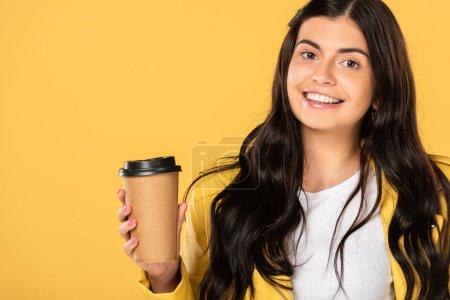 Photo pour Fille gaie attirante retenant la cuvette jetable de café d'isolement sur le jaune - image libre de droit