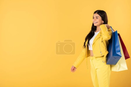 Photo for Beautiful woman with shopping bags, isolated on yellow - Royalty Free Image