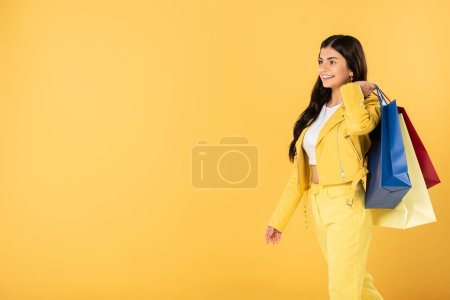 Photo for Smiling woman with shopping bags, isolated on yellow - Royalty Free Image