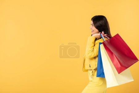 Photo pour Fille heureuse avec des sacs à provisions, d'isolement sur le jaune - image libre de droit