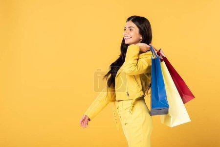 Photo pour Belle jeune femme avec des sacs à provisions, d'isolement sur le jaune - image libre de droit