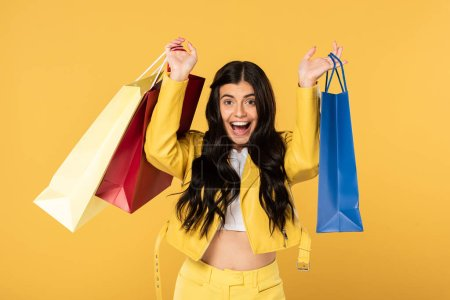 Photo for Excited beautiful woman with shopping bags, isolated on yellow - Royalty Free Image