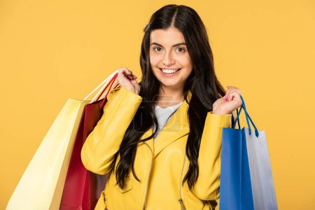 Photo for Cheerful beautiful woman holding shopping bags, isolated on yellow - Royalty Free Image
