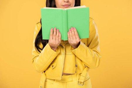Photo pour Vue recadrée du livre de lecture de l'élève, isolé sur jaune - image libre de droit