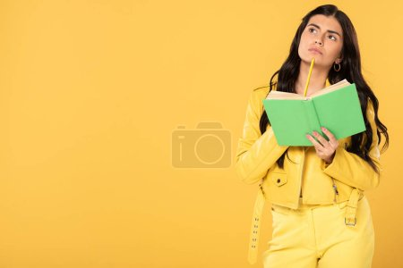 Photo for Pensive girl holding pencil and book, isolated on yellow - Royalty Free Image