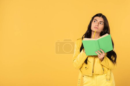 Photo for Thoughtful student holding pencil and book, isolated on yellow - Royalty Free Image