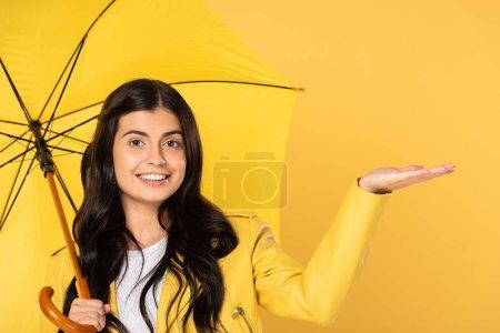 beautiful girl posing with umbrella, isolated on yellow