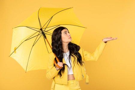 Photo pour Belle fille réfléchie posant avec parapluie, isolé sur jaune - image libre de droit