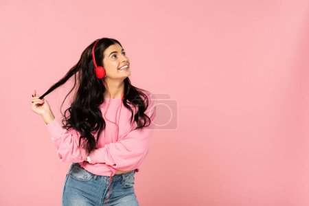 Photo for Beautiful girl listening music with headphones, isolated on pink - Royalty Free Image