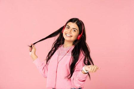 Foto de Chica sonriente escuchando música con auriculares, aislada en rosa - Imagen libre de derechos