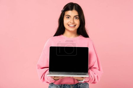 Photo for Cheerful girl showing laptop with blank screen, isolated on pink - Royalty Free Image