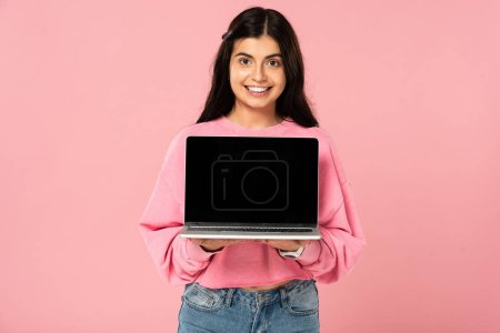 Photo for Beautiful girl showing laptop with blank screen, isolated on pink - Royalty Free Image