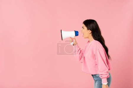 Photo for Beautiful girl yelling into megaphone, isolated on pink - Royalty Free Image